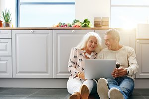 Senior people using laptop in kitchen.