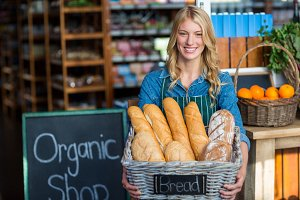 Smiling woman holding a basket of baguettes in organic shop