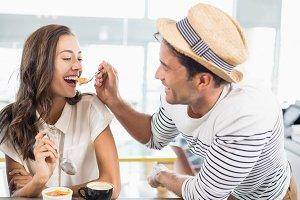 Smiling couple eating dessert