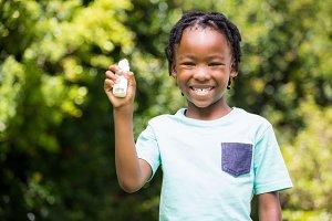 Boy showing his asthma inhaler