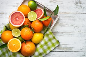 Citrus fruit in wooden tray on white table.