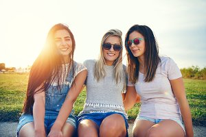 Three beautiful female friends against sunny landscape