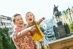 mother and child travellers in Prague pointing on something