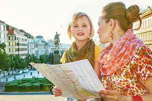 mother and child travellers with map on Wenceslas Square, Prague