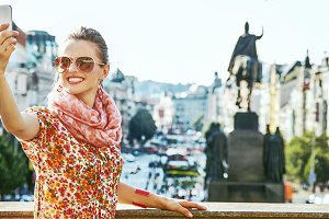 happy woman taking selfie with cellphone in Prague