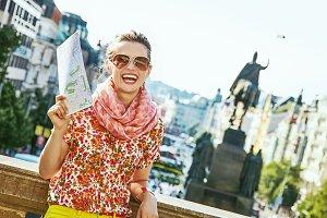 happy traveller woman on Vaclavske namesti in Prague with map