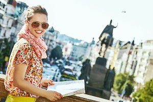 smiling young tourist woman in Prague Czech Republic with map
