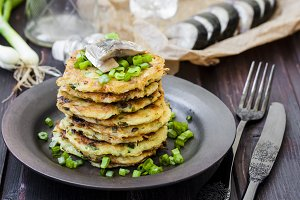 Fried potato pancakes with herring on a dark background
