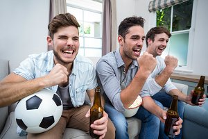Cheerful male friends watching soccer match on TV
