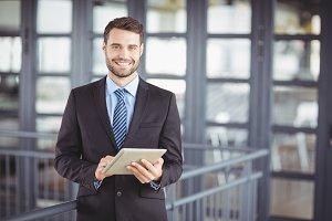 Businessman smiling while using digital tablet