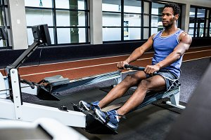 Muscular man using rowing machine