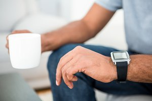 Close-up of man on coffee break with smart watch