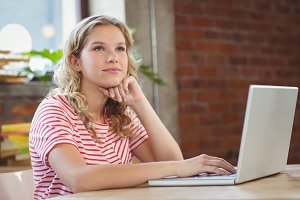 Thoughtful woman using laptop in office