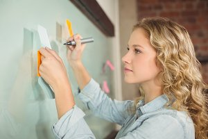 Beautiful woman holding sticky note while writing on glass board