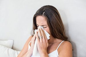 Woman sneezing with tissue on mouth