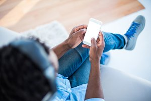 High angle view of man holding smartphone while sitting on sofa