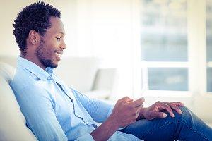 Smiling man using mobile phone while sitting