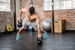 Shirtless man lifting kettlebell