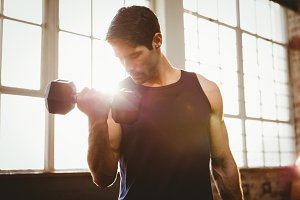 Handsome man lifting dumbbell