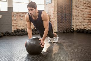 Man doing push ups on medicine ball