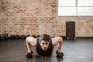 Man doing push up holding dumbbell