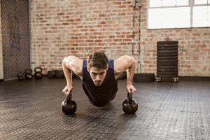 Man doing push ups holding kettlebell