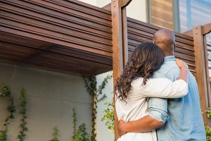 Couple with arms above after buying house