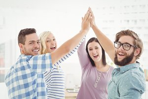 Portrait of smiling business people giving high five