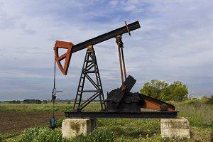 Oil derrick pumps petroleum on the field