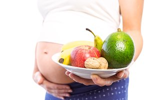 Pregnant woman showing fruit and veg