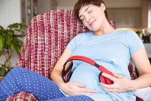 Pregnant woman putting headphones over bump
