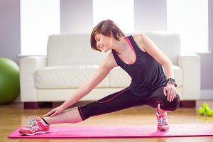 Fit woman stretching on exercise mat