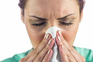 Woman suffering from cold with tissue on mouth
