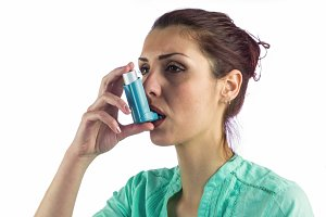 Close-up of woman using asthma inhaler