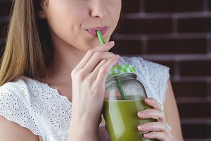 Pretty woman sipping on green juice