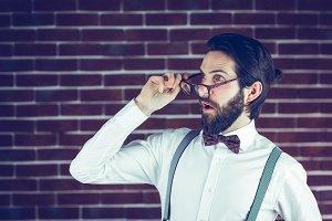 Shocked hipster holding eyeglases