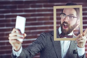 Excited man taking selfie while holding frame