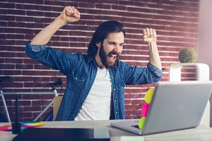 Cheerful creative businessman with arms raised looking at laptop