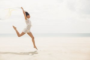 Stylish woman leaping with scarf