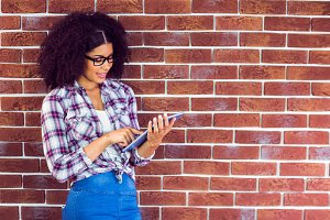 Attractive hipster leaning on wall and using tablet