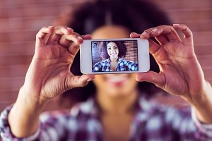 Attractive young woman taking selfies with smartphone