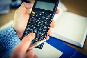 Businessman hands typing on calculator