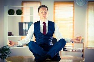 Calm businessman meditating in lotus pose