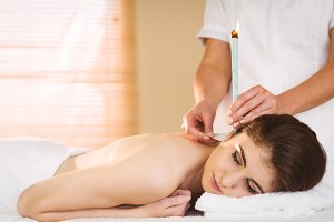 Young woman getting ear candling treatment