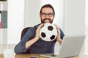 Hipster businessman holding a football