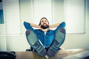 Hipster businessman relaxing at his desk
