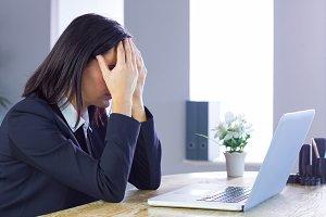 Stressed businesswoman working at her desk