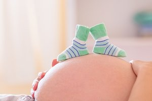 Pregnant woman with baby shoes over bump