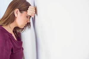 Depressed woman leaning her head against a wall