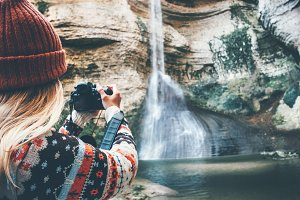 Woman taking photo of waterfall